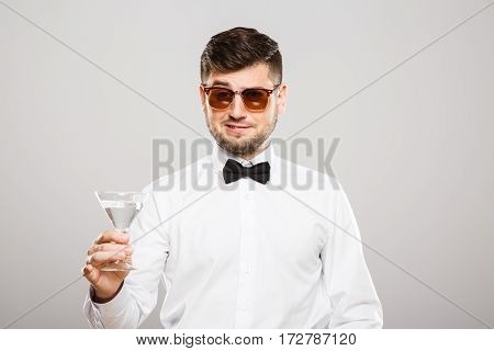 Man with black hair and beard wearing white shirt with bowtie and sunglasses at gray studio background and holding glass of alcohol.