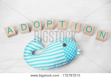 Cubes with word ADOPTION and whale toy on light wooden background