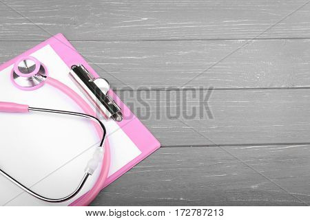 Stethoscope with clipboard on wooden table