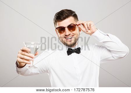 Handsome man with black hair and beard wearing white shirt with bowtie and sunglasses at gray studio background and holding glass of alcohol.