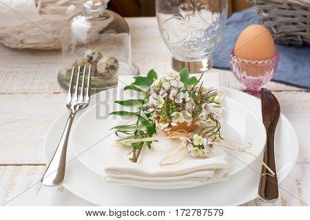 Table setting for Easter white plates napkin bouquet of white flowers green leaves quail eggs crystal blue linen outdoors kinfolkelegant