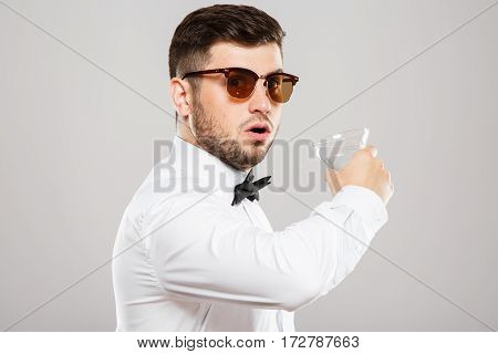 Attractive man with black hair and beard wearing white shirt with bowtie and sunglasses at gray studio background, copy space.