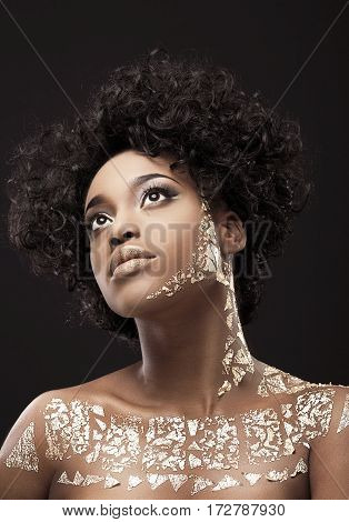 Portrait of beautiful African American girl with dark curly hair. Make-up, hairdo, gold. Covered with golden patterns. Looking up. Head and shoulders, indoors, studio