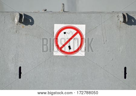 A sign prohibiting Smokinghanging on a metal wall.
