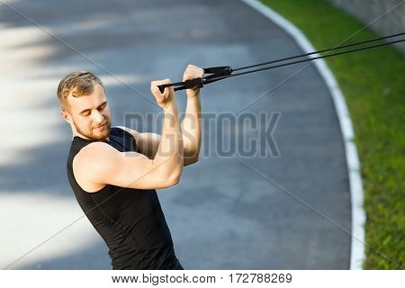 Man training with expander hooked on fence, looking down. Muscular sportsman pulling expander to himself, deflecting back. Sport, outdoors, stadium, waist up