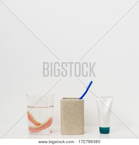 Blue tooth brushe in ceramic glass, paste tube, dental plates in a glass with water at the bathroom