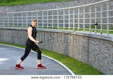 Full body of man training with expander hooked on fence. Muscular sportsman pulling expander to himself and looking down. Sport, outdoors, stadium