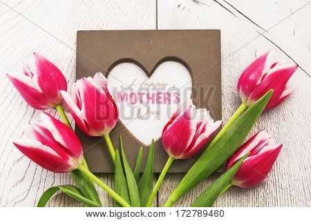 Pink tulips and frame on white wooden background
