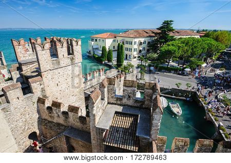 Sirmione, province of Brescia, Lombardy, northern Italy - 15th August 2016: people visiting the medieval castle Scaliger on lake Lago di Garda