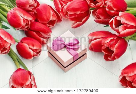 Spring tulips with gift on wooden background