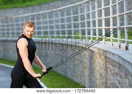 Man training with expander hooked on fence. Muscular sportsman pulling expander to himself and looking down. Sport, outdoors, stadium