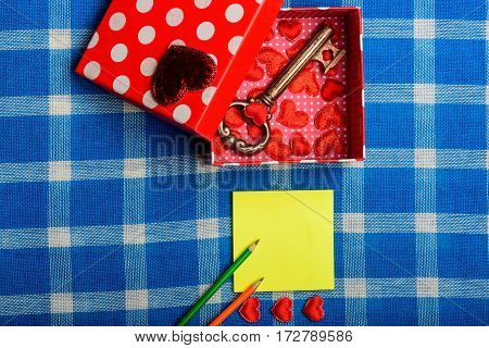 cute and beautiful present box with heart symbol of love metallic key yellow note paper green and orange pencils on white and blue plaid fabric or checkered cloth background copy space