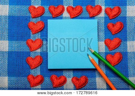 green and orange pencils on blue note paper surrounded by small sweet red hearts symbol of love on white and blue plaid fabric or checkered cloth background copy space