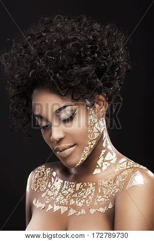 Portrait of beautiful African American girl with dark curly hair. Make-up, hairdo. Covered with golden patterns. Looking down. Head and shoulders, indoors, studio