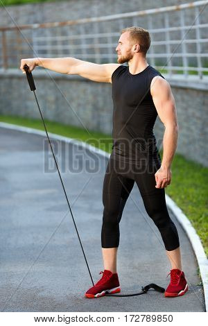 Profile of man training with expander. Muscular sportsman standing on expander with one leg and holding it with one hand, pulling it to himself. Full body, outdoors, stadium