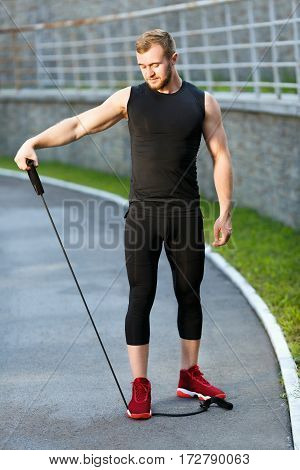 Man training with expander. Muscular sportsman standing on expander with one leg and holding it with one hand, pulling it to himself and looking down. Full body, outdoors, stadium
