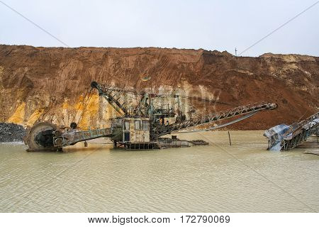Clay quarry near the town of Polohy in the Zaporizhya region of Ukraine. Rotary excavator  for the extraction of clay flooded by torrential rains. March 2006