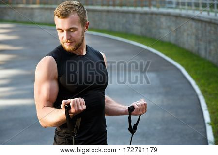 Waist up of man training with expander, looking down. Muscular sportsman holding expander with both arms, pulling it to himself. Full body, outdoors, stadium