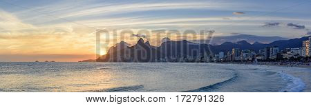 Summer sunset at Ipanema beach in Rio de Janeiro with Leblon beach Two Brothers hill and Gavea stone at bacjground