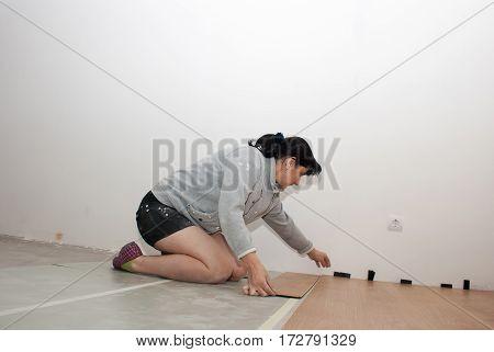 young beautiful woman puting laminate flooring at home