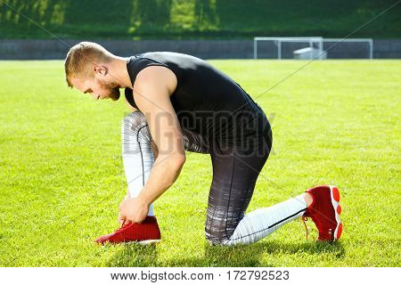 Man leaning on one knee on grass and tightening lacings of red sneaker. Profile of sportsman resting on stadium. Full body, outdoors, stadium