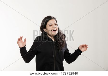 Very surprised girl with her arms raised, portrait in studio