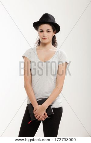 Girl with a black hat and t-shirt, studio portrait