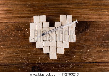 Diabetes is terrible disease. Heart of sugar cubes with syringe.