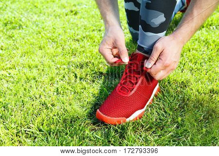 Sport concept, sport shoes. Man tightening lacings of red sneaker, without head. Green grass, outdoors, stadium, only legs