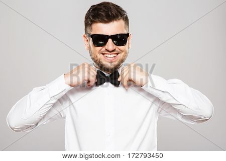Attractive man with black hair and beard wearing white shirt with bowtie and sunglasses at gray studio background, portrait, copy space, posing.