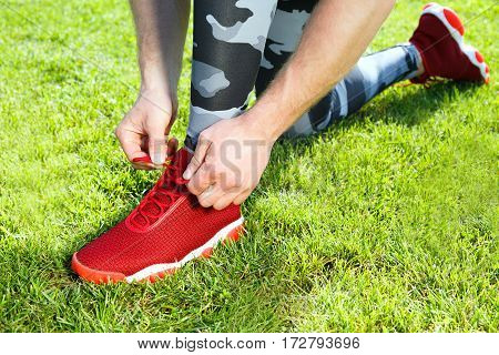 Sport concept. Man tightening lacings of red sneakers, one leg ahead. Without head. Green grass, outdoors, stadium, only legs