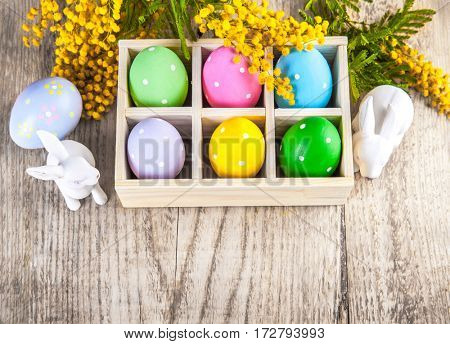 Easter eggs branch mimosa and white rabbit on wooden board rustic style with copyspace