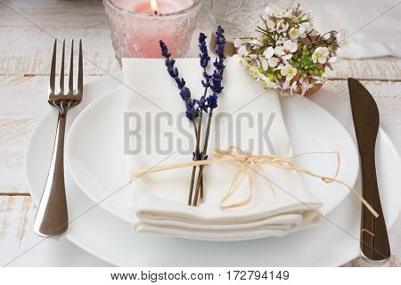 Romantic table setting wedding lavender white small flowers plates napkin lit candle wood table outdoors kinfolk authentic elegant