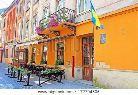 LVIV, UKRAINE - JUNE 30, 2014: Typical street cafe near the historic stone house of Bohushivska. Due to comprehensive cultural programme and tourism infrastructure Lviv is very popular distination
