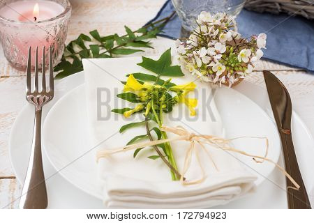 Wedding table setting elegant white yellow flowers green leaves candle plates blue napkin wood table outdoors kinfolk romantic