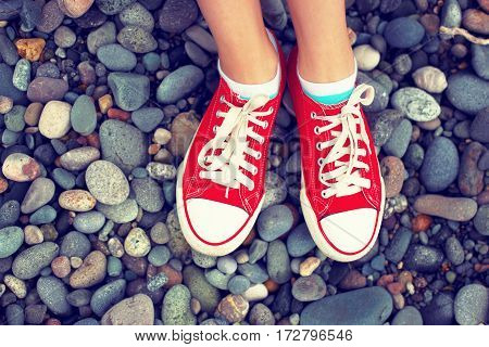 Sneakers,vacation,beach.Journey.Photo toned in retro style.Abstract image of legs in shoes on a pebble beach.