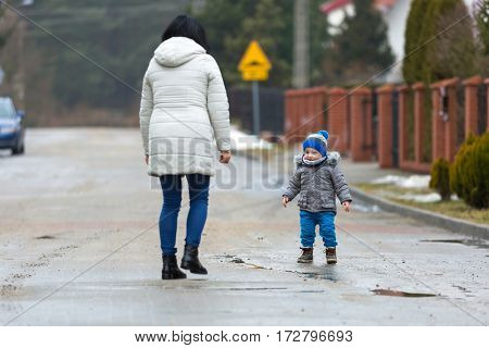 Little toddler boy walking with his mother on the sidewalk