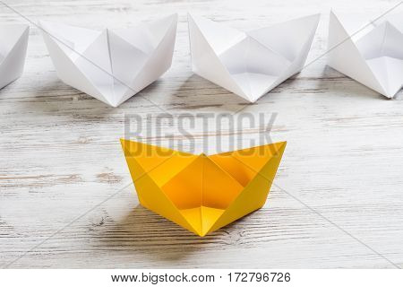 Set of origami boats on wooden table, one yellow and the rest are white.