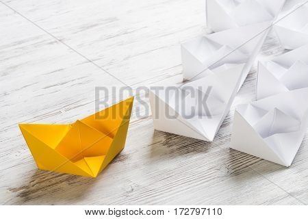Set of origami boats on wooden table, one yellow, the rest are white.