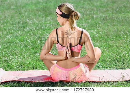 Girl stretching on mat in park. Rear view of girl in rose training suit doing yoga asana, sitting on mat, hands folded together behind the back, namaste. Outdoors, closeup, rear view
