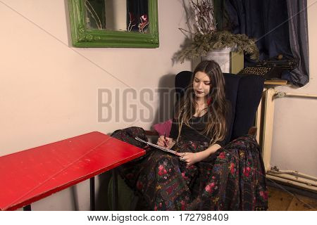 Girl sitting behind table and write. Papers are on her knees.