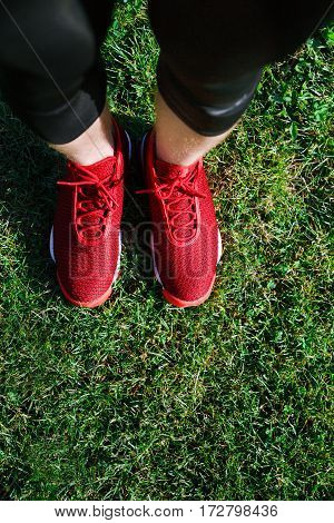 Sport concept, red sneakers for running. Man standing on grass, no face. Legs in professional sport shoes. Outdoors, sunlight, pitch, field