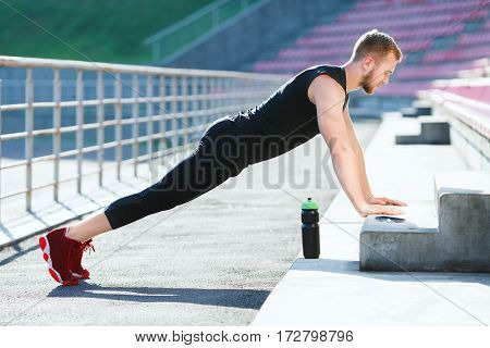 Full body of sportsman doing plank on stadium. Profile of man in black training suit and red sneakers standing in plank position. Outdoors, sunlight, stadium, doing sport