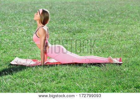 Girl stretching on mat in park. Profile of young woman with closed eyes in rose training suit doing yoga, cobra asana, bhujangasana. Girl leaning on hands, stretching legs. Outdoors, nature