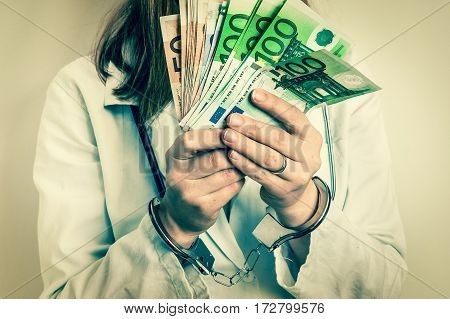 Doctor with euro money and handcuffs - corruption and bribe concept in medicine - retro style