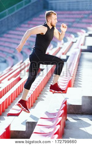 Full body of sportsman running up on tribune of stadium. Profile of man in black training suit and red sneakers. Outdoors, stadium, sport, sunlight