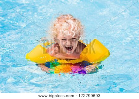 Happy laughing little boy playing in outdoor swimming pool on a hot summer day. Kids learn to swim. Child with colorful floaties and floating kickboard. Family vacation in tropical resort.