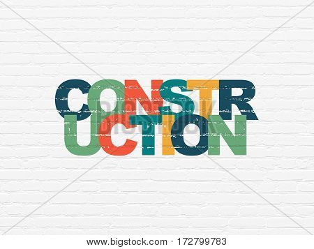 Constructing concept: Painted multicolor text Construction on White Brick wall background