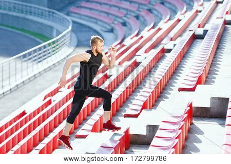 Full body of man running up on tribune of stadium. Profile of sportsman in black training suit and red sneakers. Outdoors, sunlight, stadium, doing sport