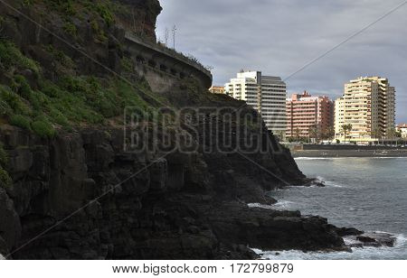 Puerto de la Cruz with hotels and beach in background and rocky seashore in foreground picture from Tenerife Spain.